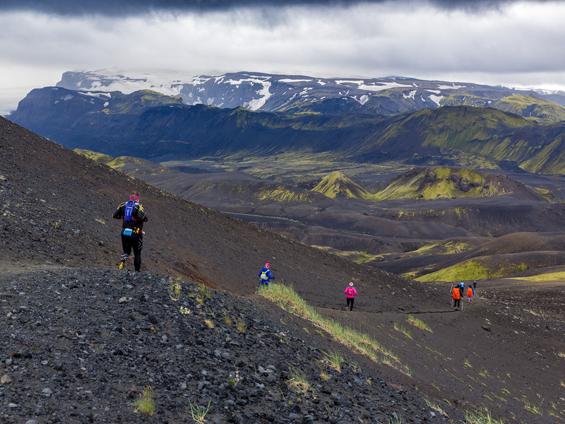 Participants running in black sand with view of beautiful mountains