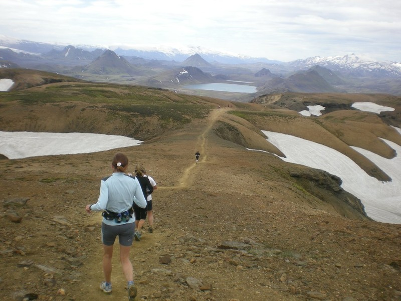 Participants running down hill with sight of lake Álftavatn